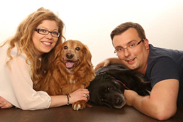 Tierfoto Frau mit Hund, die einem Mann mit Hund gegenüber auf dem Bauch liegt.