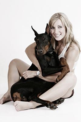 Tierfoto junge, sitzende Frau, die ihren Dobermann zwischen den Beinen hält und umarmt vor hellem Hintergrund.