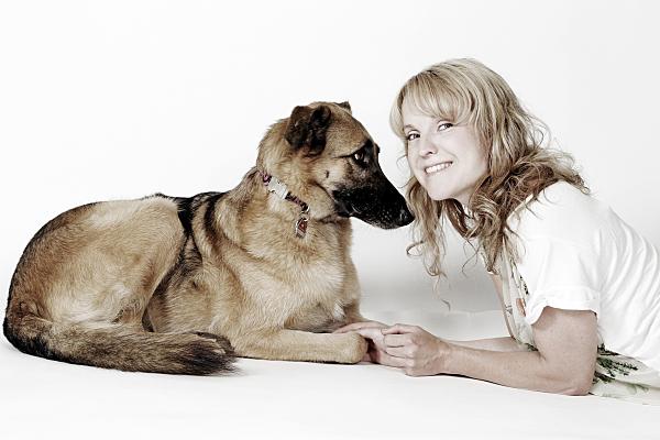 Tierfoto auf dem Bauch liegende Frau neben Schäferhund vor hellem Hintergrund.