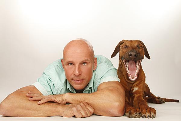 Tierfoto auf dem Bauch liegender Mann neben gähnendem Hund vor hellem Hintergrund.