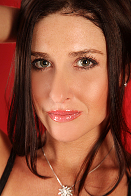 Beautyshooting junge Frau mit dunklen Haaren, die sie hochrafft vor rotem Hintergrund.