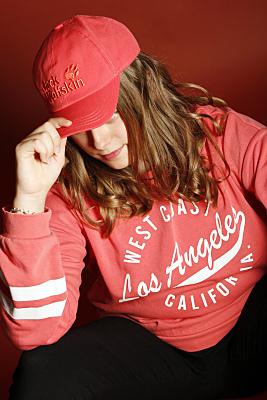 Beautyshooting junge Frau mit dunklen Haaren und rotem Cap.