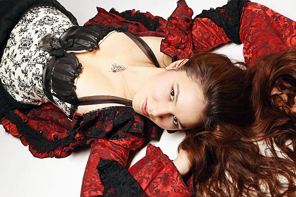 Beautyshooting junge, auf dem Rücken liegende Frau mit dunklen Haaren und Spitzenkorsage sowie rotem Satinmantel an.