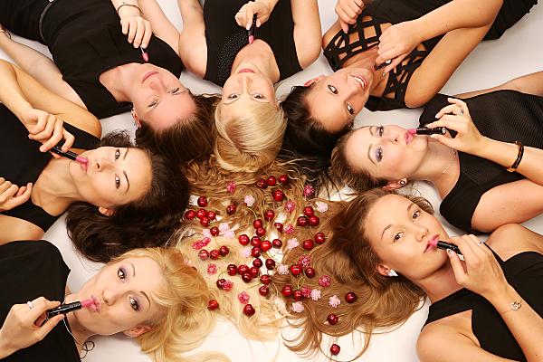 Beautyshooting sieben lächelnde, auf dem Rücken mit den Köpfen einen Kreis bildend liegende Frauen mit Kirschen in der Mitte und Lippenstiften in den Händen.