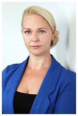 Bewerbungsfoto Frau mit blonden Haaren und Zopf vor hellem Hintergrund.