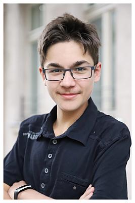 Bewerbungsfoto junger Mann mit Brille in dunklem Hemd vor Hausfassade.
