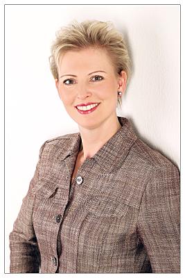 Bewerbungsfoto Frau mit kurzen, blonden Haaren vor hellem Hintergrund.