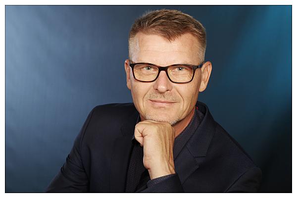 Bewerbungsfoto Mann mit Brille in Hemd vor grauem Hintergrund, der seine Hand ans Kinn hält.