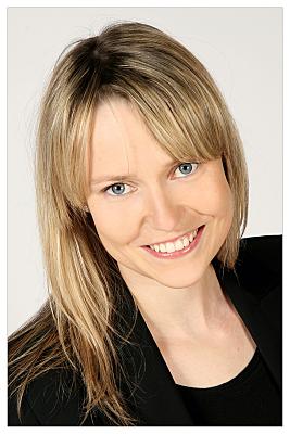 Bewerbungsfoto Frau mit offenen, blonden Haaren vor hellem Hintergrund.