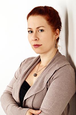 Businessfoto Frau mit Zopf in grauem Jacket vor hellem Hintergrund.