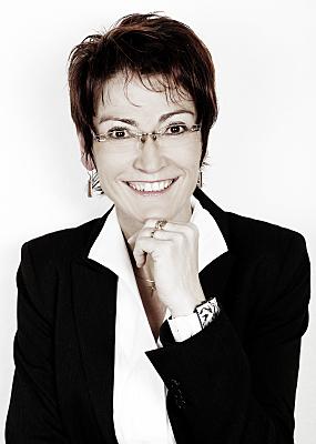 Low Key Businessfoto Frau in Bluse und Jacket vor hellem Hintergrund, die ihre Hand ans Kinn hält.
