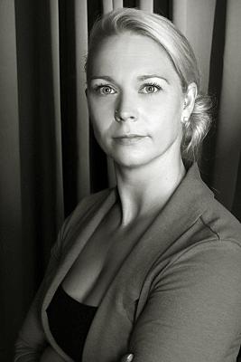Low Key Businessfoto Frau in Bluse und Jacket vor grauem Hintergrund.