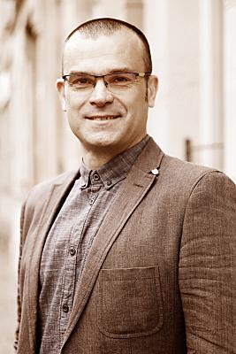 Low Key Businessfoto Mann mit Brille in hellem Hemd und Jacket vor Hausfassade.