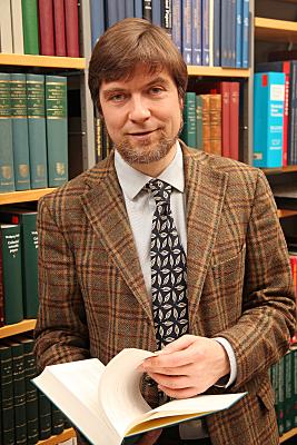Businessfoto Mann in hellem Hemd mit Buch, Schlips und kariertem Jacket vor einer Bücherwand.