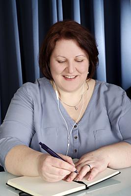 Businessfoto Frau, die in ein Notizbuch schreibt.