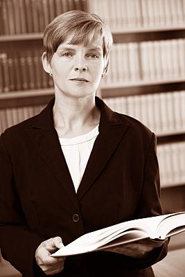 Low Key Businessfoto Frau in heller Bluse und schwarzem Jacket vor einer Bücherwand.