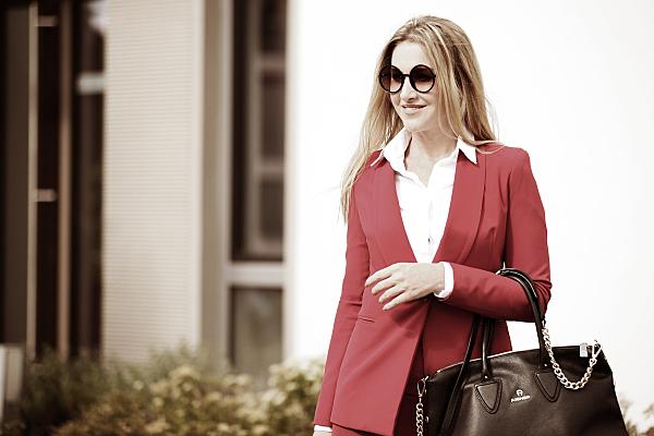 Businessfoto Frau mit Sonnenbrille und dunkler Handtasche in heller Bluse und rotem Jacket vor einer Hauswand.