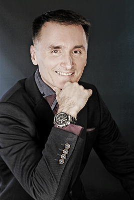Businessfoto Mann mit Brille in Hemd vor grauem Hintergrund, der seine Hand ans Kinn hält.