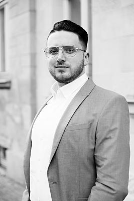 Low Key Businessfoto junger Mann mit Brille in hellem Hemd vor Hausfassade.