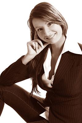 Low Key Businessfoto Frau in heller Bluse und Jacket, die ihre Hand ans Gesicht hält.