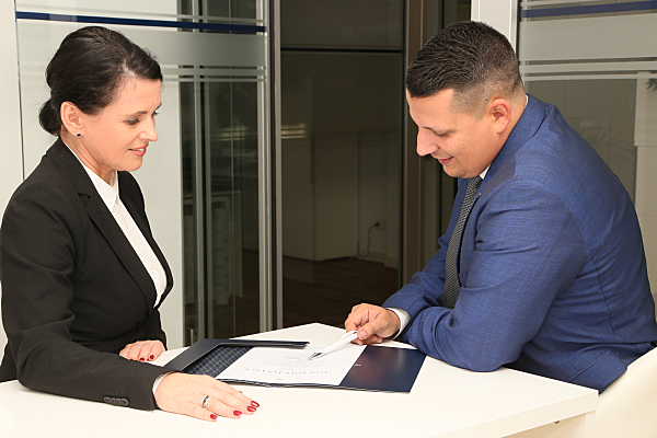 Businessfoto Frau und Mann an einem Schreibtisch über Akten gebeugt.