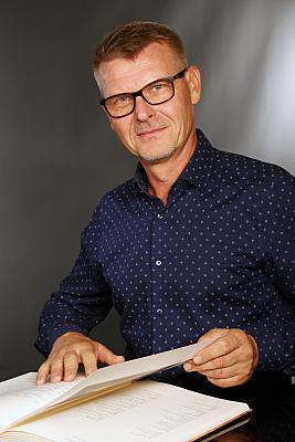Businessfoto Mann mit Brille in Hemd vor grauem Hintergrund.