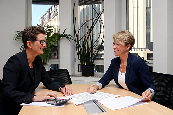 Businessfoto zwei Frauen an einem Schreibtisch in dunklen Anzügen.