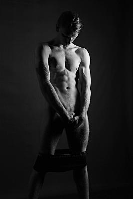Schwarz-weißes Aktfoto eines stehenden Mannes, der seine Hände in seine dunkle Boxershorts schiebt und nach unten schaut.