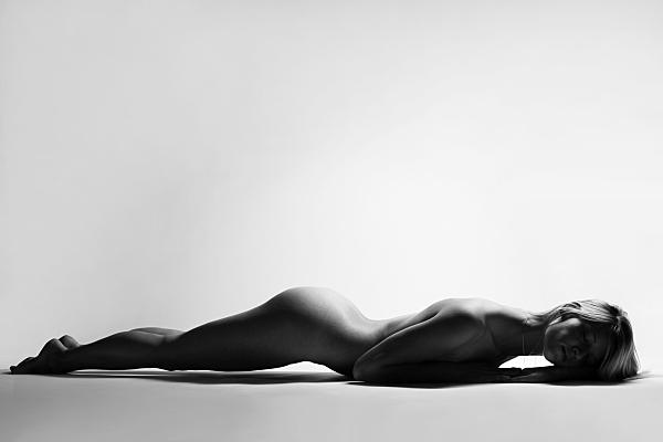 Schwarz-weiß Aktfoto auf dem Bauch liegende Frau, die ihren Po in die Luft reckt und ihren Kopf auf ihrem Arm ablegt..