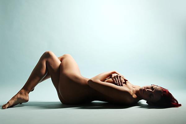 Aktfoto auf dem Rücken liegende Frau, die ihre Beine anstellt und mit den Händen ihre Brüste verdeckt.