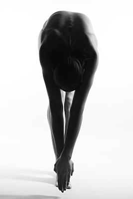 Aktfoto stehende Frau, die ihren Oberkörper nach vorne beugt und ihre Hände Richtung Zehen reckt.