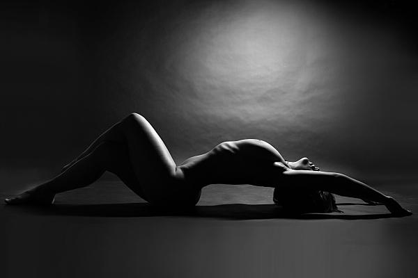 Schwarz-weiß weiß Aktfoto auf dem Rücken liegende Frau, die ihre Beine anstellt, ihre Arme über den Kopf streckt und ihren Rücken durchbiegt.