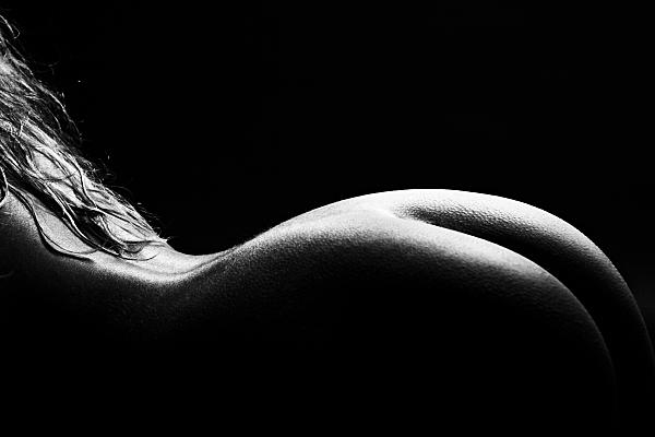 Schwarz-weiß Aktfoto einer auf dem Bauch liegenden, blonden Frau vor schwarzem Hintergrund.