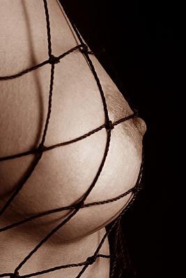 Aktfoto Detail nackter Frauenbrust mit grobem Netz.