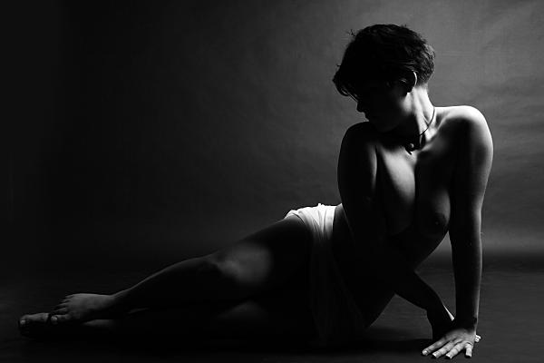 Schwarz-weiß Aktfoto auf der Seite liegende Frau vor dunklem Hintergrund.