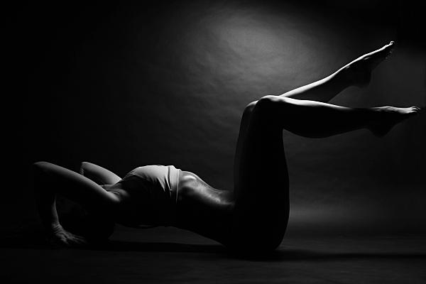Aktfoto einer schlanken Frau auf einem Stepper liegend mit weißem, bauchfreien Top, die Arme über den KOpf gereckt, den Stepper umfassend, die Beine angewinkelt in die Luft gereckt.