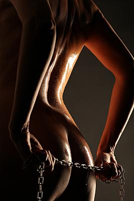Aktfoto Detail nackter Rücken und Po einer Frau, die eine Gliederkette zwischen den, auf den Rücken gedrehten Händen, hält.