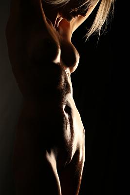 Aktfoto Detail nackter Frauentorso vor schwarzem Hintergrund.