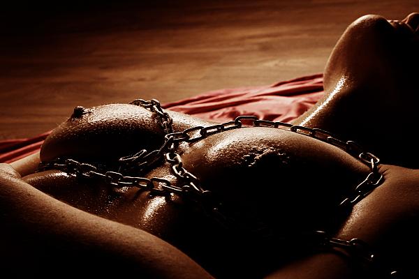 Aktfoto Detail nackter Frauenoberkörper mit Gliederkette um Hals und Brüsten.