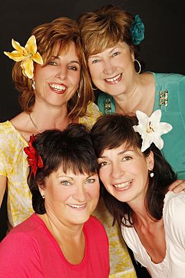 Freundefoto vier Frauen mit großen Lilienblüten im Haar, die in zwei Reihen hintereinander stehen.