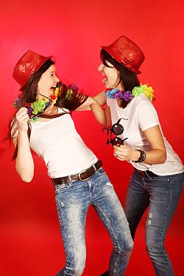 Freundefoto zwei lachende Frauen in weißen Tops mit Deutschland-Boa und rotem Hut vor rotem Hintergrund.