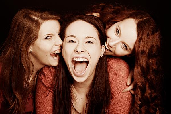 Freundefoto zwei Frauen, die andeuten einer in der Mitte stehenden Frau ins Ohr zu beissen.