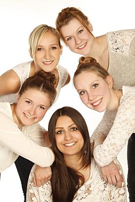 Freundefoto vier lächelnder Frauen vor weißem Hintergrund.