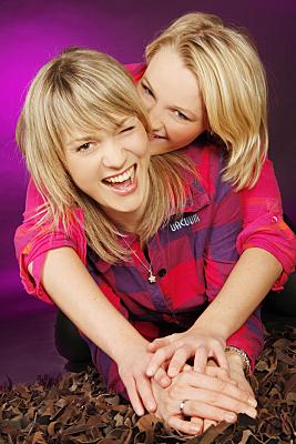 Freundefoto zweier lachender Frauen vor lila Hintergrund.
