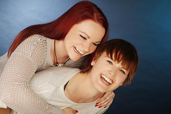 Freundefoto zweier lachender Frauen vor blauem Hintergrund.