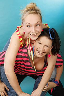 Freundefoto zweier lächelnder Frauen vor blauem Hintergrund.