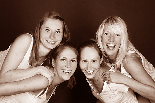 Low Key Freundefoto vier Frauen, von denen zwei jeweils auf dem Rücken der anderen lehnen.