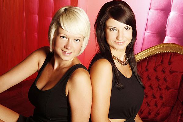 Freundefoto zweier lächelnder Frauen, die sich aneinander lehnen, vor rotem Hintergrund.
