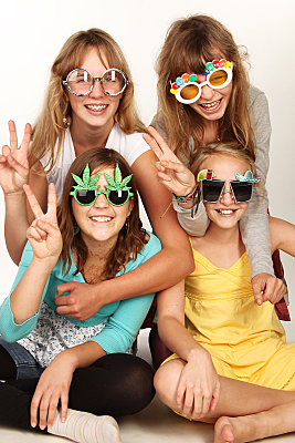 Freundefoto vier lächelnder Frauen vor hellem Hintergrund mit lustigen Sonnenbrillen.