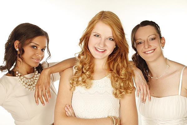 Freundefoto drei Frauen nebeneinander stehend in hellen Oberteilen.